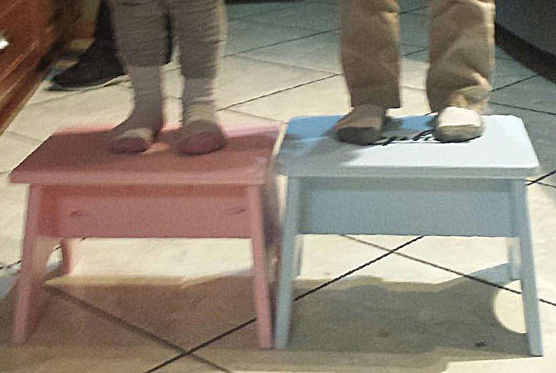Lower Legs and Feet of Two Children Standing on Two Stools.